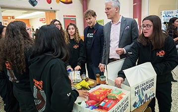 St. Thomas More students box food donations with Marc Kielburger and Dean Stoneley.