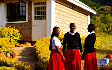 Local students outside of a WE Villages school building