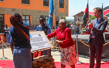 The First Lady of Kenya with a plaque at WE College.