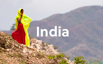 Local girl in traditional clothing overlooking mountainous landscape in India