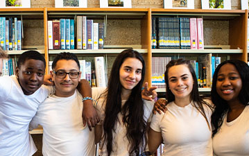 Students from Mather High posing together in a library
