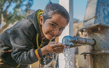 Boy drinking from water tap