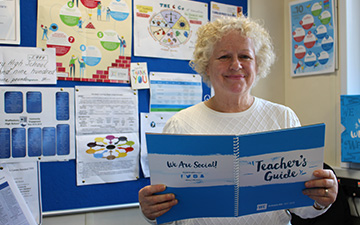 Debbie Stone in her classroom with her WE Schools Teacher's Guide.