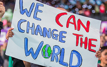 "A sign in the WE Day audience reads ""WE CAN CHANGE THE WORLD."""