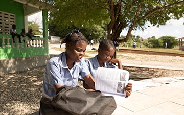Haitian students study outside.