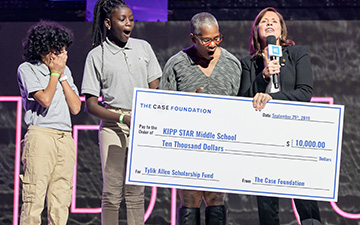 Jean Case surprises a teacher and students from Kipp Star Middle School with a check for $10,000 on stage at WE Day UN.