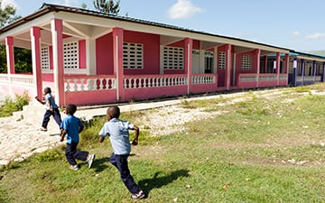 Haitian students play outside a new school built by WE.