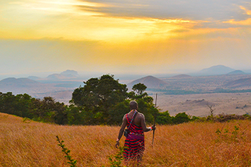 Maasai Warrior walking through grassy field