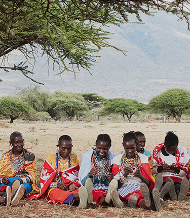 Local women beading under acacia tree in Kenya