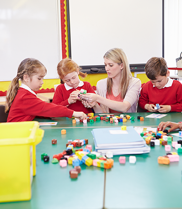 A teacher and students using blocks to learn maths