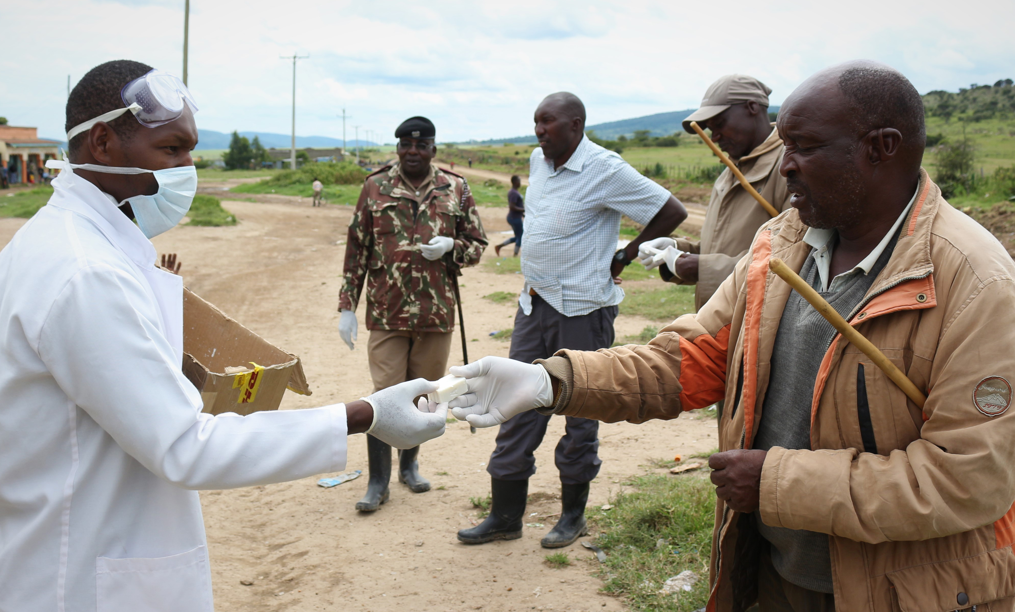 Duke Ongori, who runs WE's mobile medical units, hands out soap while the Area Chief observes, part of the community awareness campaign to explain best practices.