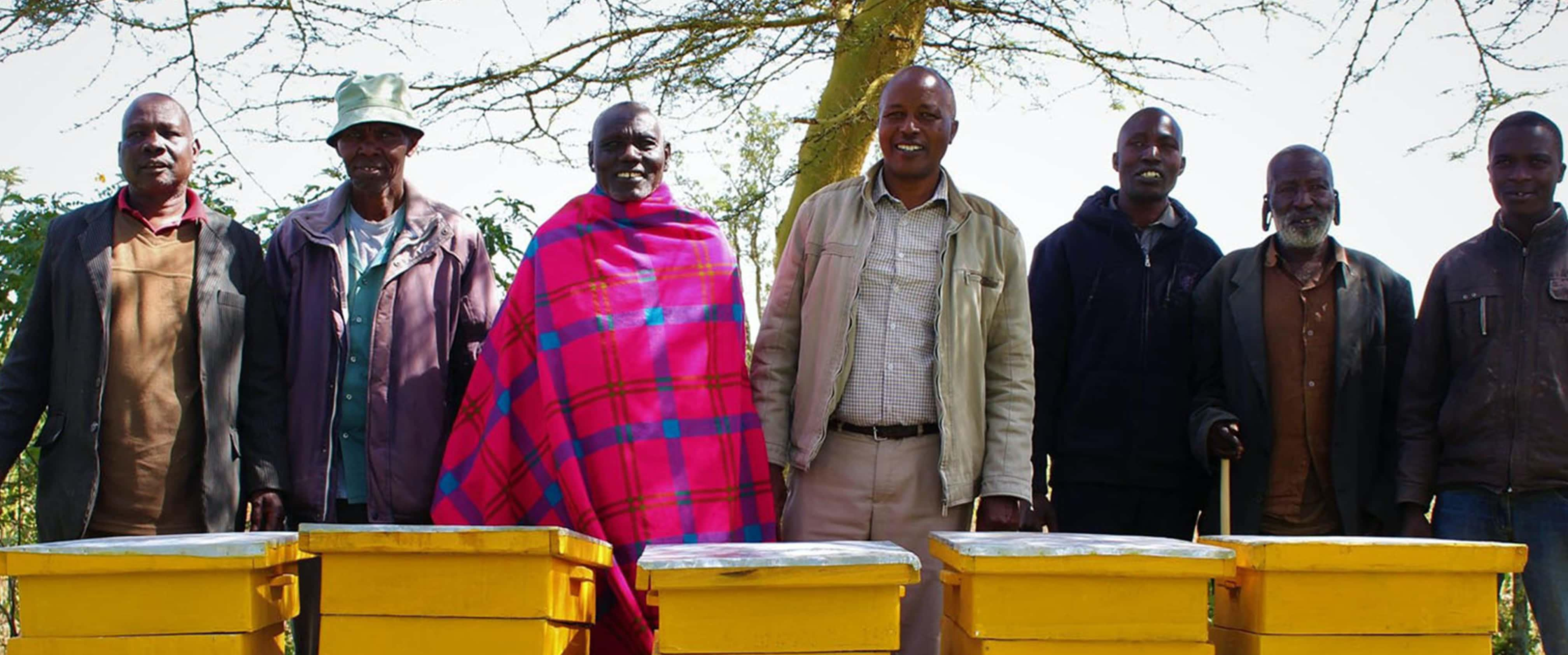 Beekeepers smiling, standing with beehives