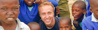 Craig Kielburger posing for picture with local kids in Kenya