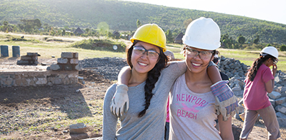 Young travellers posing for a picture while volunteering on a build site