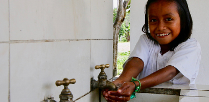 Young student cupping water from tap in Ecuador