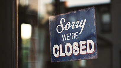 "A sign in a storefront window that says ""Sorry we're closed"""
