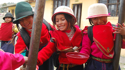Two school children in Ecuador collect water fro a water pump.