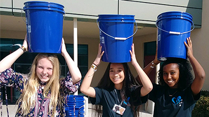 Students hold buckets on their heads during WE Walk for Water.