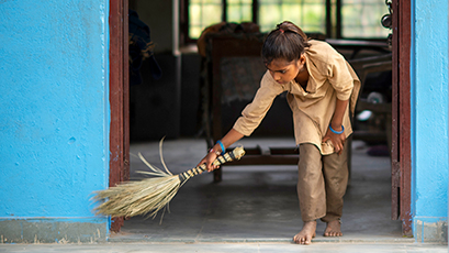 A young girl sweeping the floor in India