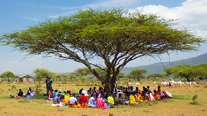 Local Kenyan women beading under acacia trees in the daytime