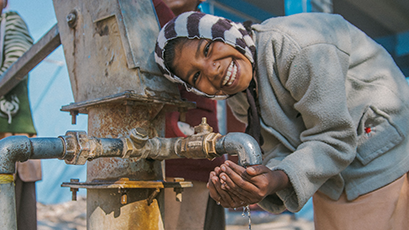 Local girls around a water pump in India