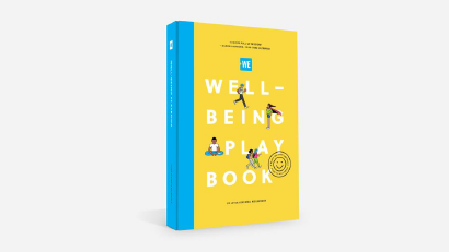 The WE Well-being playbook, which is bright yellow with a blue spine, standing up on a white background