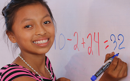 A student learning math at a whiteboard