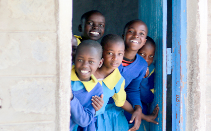 Children smile out the window of their classroom