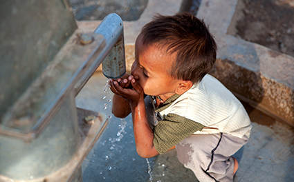 Kenyan child drinking from a new water pump