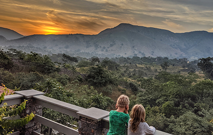 Two of Michelle's children watching the sun set behind a mountain.