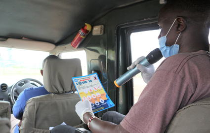 A man provides mobile COVID-19 prevention education.