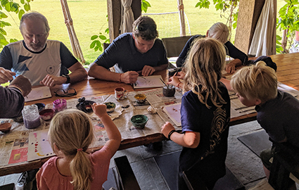 The family sitting at a long table, painting.