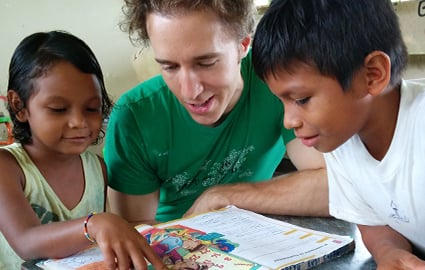 Craig Kielburger reading with local students at a newly finished school in Ecuador