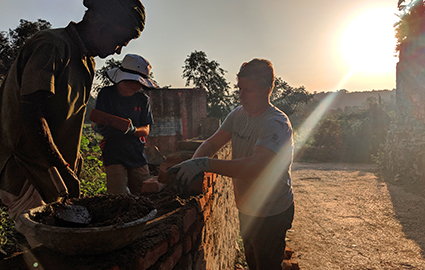 Greg and Luke helping a community member build a brick wall at sunset.