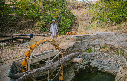 Farmer beside water project, India
