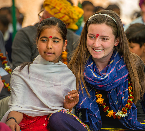 Young traveller and local girl in India