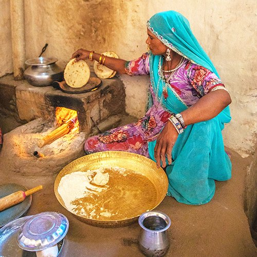 Local woman cooking chapatti in home in India