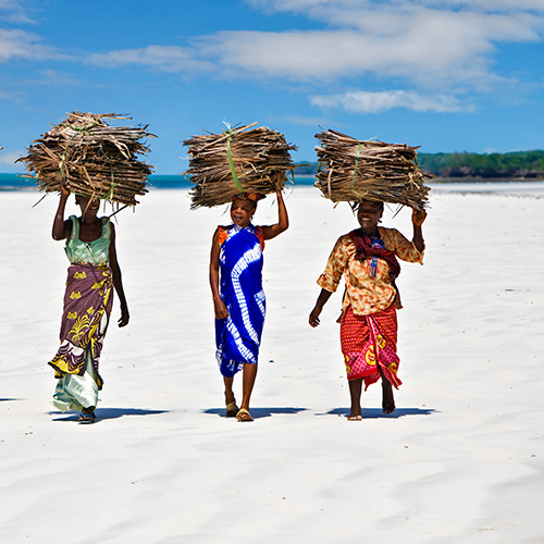 Locals carrying bundles of sticks on head, walking down beach on Kilifi Coast