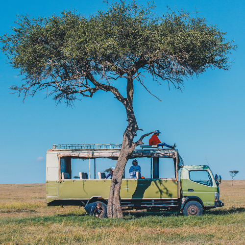 Travellers sitting in a jeep under an acacia tree in Kenya