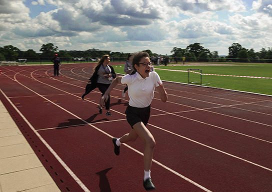 A student runs on an outdoor track.
