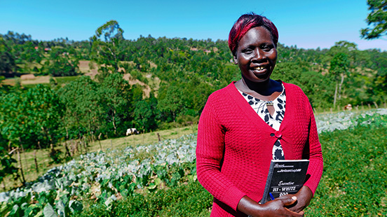 Mary Koech standing in tea field in Kenya
