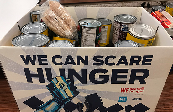 Cans of food in a WE Scare Hunger box.