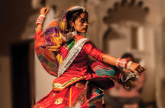 Local woman in traditional clothing dancing in India