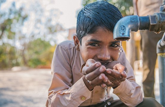 Local boy drinking water from tap in India