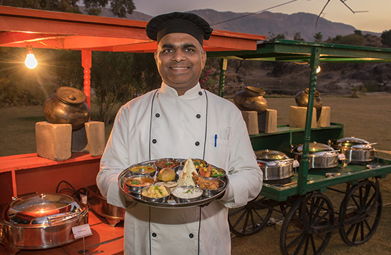 Local chef holding spread of traditional India food