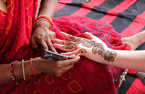 Local woman drawing henna on traveller's hand in India