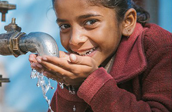 Student drinks from a clean water tap in rural India.