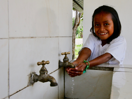 Young local girl cupping her hands catching water under a tap