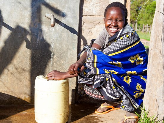 Young community member collecting water in a jug from a tap in Kenya