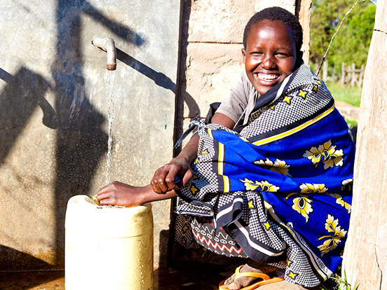 Local Kenyan woman in traditional clothing collecting water in a jug from a tap